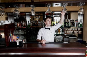 Young handsome bartender working in front of the bar